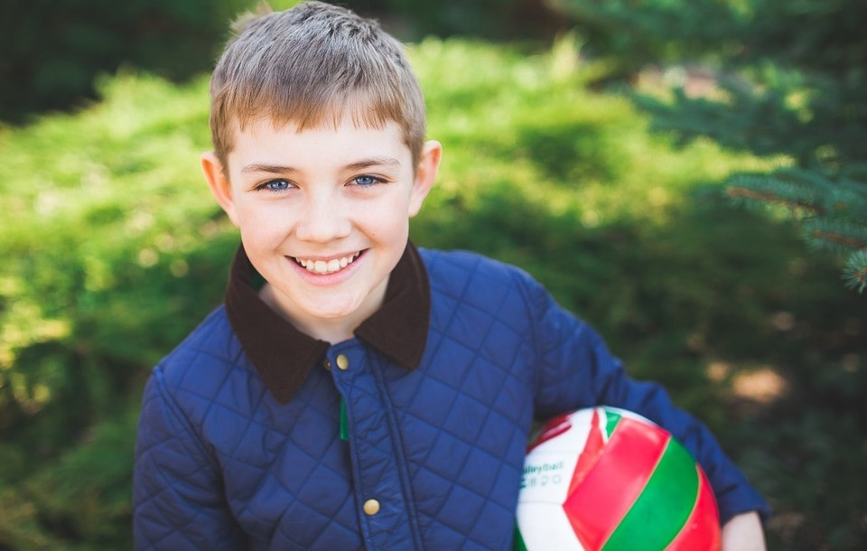 Kid holding ball and smiling